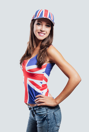 british girl: Smiling British girl looking at camera, she is wearing a British flag cap and tank top
