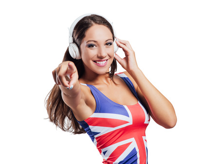 british girl: Cheerful pop girl wearing a British flag top, listening to music on white background Stock Photo