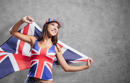 union flag: Cheerful cute English girl holding a flag, wearing a tank top and a cap with Union Jack flag, patriotism and enjoyment concept Stock Photo