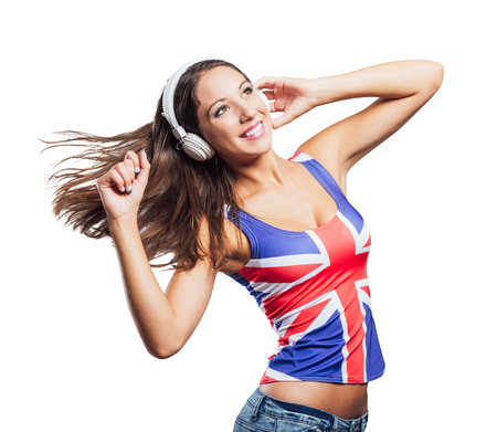 english girl: Smiling teenager girl wearing an English flag tank top, she is listening to music with headphones and dancing