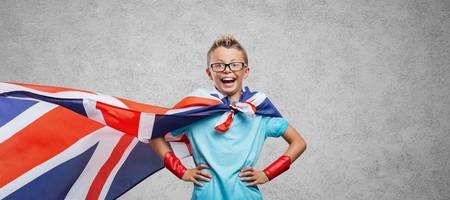 languages: Cute smiling superhero boy posing with arms akimbo and wearing a British flag as a cape, learning languages concept