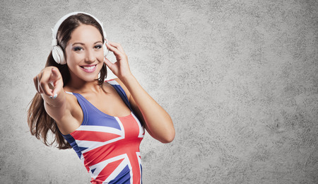 british girl: Cheerful pop girl wearing a British flag top, listening to music with headphones and dancing Stock Photo