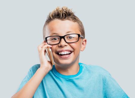 niños sonriendo: Muchacho joven sonriente con una llamada telefónica con su teléfono inteligente de pantalla táctil Foto de archivo