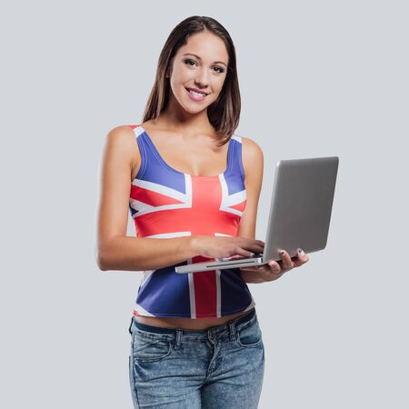 british girl: Smiling girl wearing a British flag tank top and using a laptop Stock Photo
