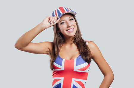 british girl: Smiling British girl looking at camera and wearing a British flag cap and tank top, she is touching her cap Stock Photo