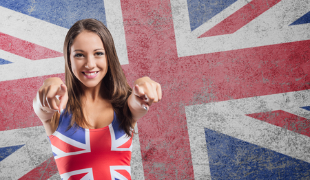 Smiling girl pointing at camera and wearing a British flag tank top