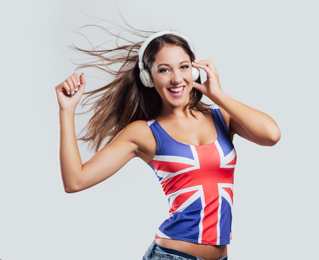 british girl: Smiling dancing girl wearing a British flag tank top and dancing, she is looking at camera