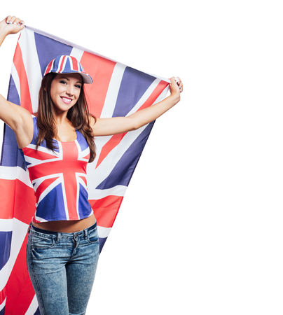 british girl: Cheerful cute British girl holding a flag, wearing a tank top and a cap with Union Jack flag, patriotism and enjoyment concept Stock Photo
