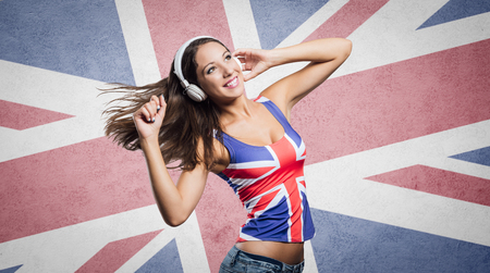 mujer alegre: Smiling teenager girl wearing an English flag tank top, she is listening to music with headphones and dancing
