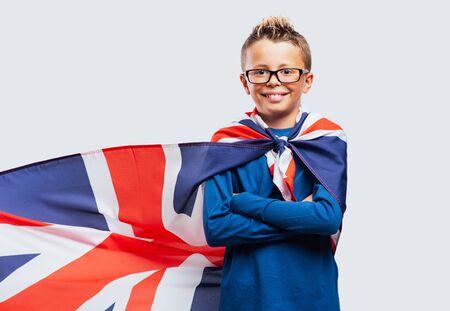 actitud: niño de superhéroes de pie con los brazos cruzados y mirando a la cámara sonriendo, él está usando una bandera británica como un cabo Foto de archivo