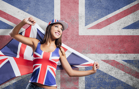english girl: Cheerful cute English girl holding a flag, wearing a tank top and a cap with Union Jack flag, patriotism and enjoyment concept Stock Photo