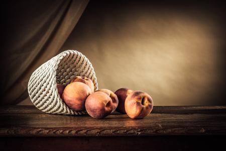 corbeille de fruits: Pêches mûres dans un panier blanc sur une table en bois rustique et drapé sur fond Banque d'images