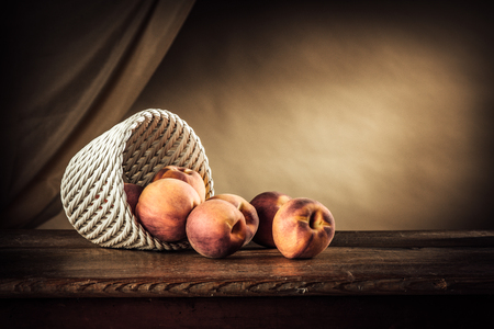 basket: Ripe peaches in a white basket on a rustic wooden table and drape on background Stock Photo
