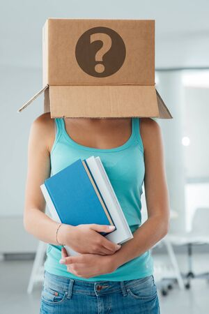 inexpressive: Insecure female student with a box on her head and a question mark, she is holding books and thinking about her future career