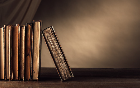 Ancient books on a wooden table and drape on background, literacy and knowledge concept