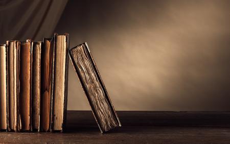 libros antiguos: Libros antiguos en una mesa de madera y la caída en el fondo, la alfabetización y el concepto de conocimiento