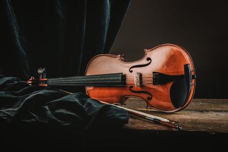 古いバイオリン弓とドレープのある静物、芸術音楽のコンセプトと素朴な木製のテーブル