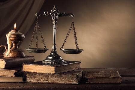 Alte Silber Skala und Hardcover-Bücher auf einem Holztisch, der Gerechtigkeit und Wissen Konzept