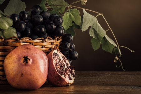 uvas: Grapes in a basket and pomegranates with vine leaves on a wooden table