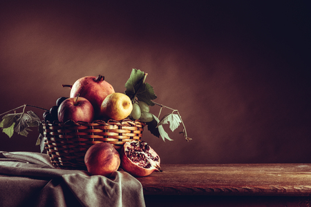 fruit basket: Seasonal ripe fruit in a basket on a rustic wooden table, vine leaves and drape Stock Photo