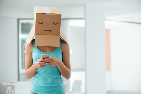 Young teen girl with a box on her head texting with her mobile phone, adolescence and social isolation concept