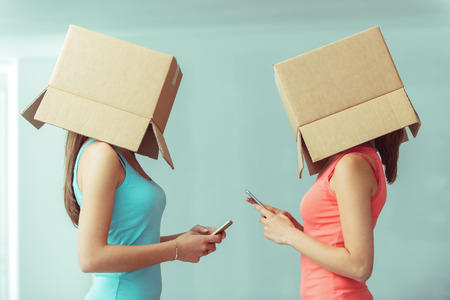 Adolescent girls with boxes on their heads texting with their smart phones, social networks and isolation concept