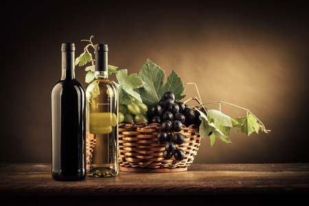 Wine bottles, grapes and vine leaves in a basket on a rustic wooden table, still life Stock Photo