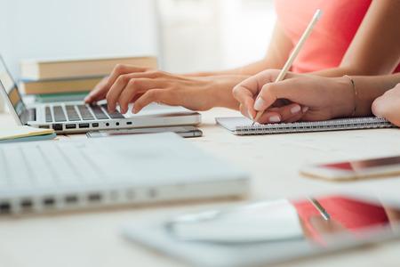 education: Teen dziewcząt studiujących na biurku i robi zadania domowe, jeden jest za pomocą laptopa, a drugi jest pisanie na notebooku, koncepcja edukacji, nierozpoznawalne ludzi Zdjęcie Seryjne