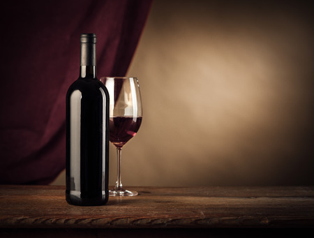 Red wine bottle and glass on a rustic wooden table, red cloth on background