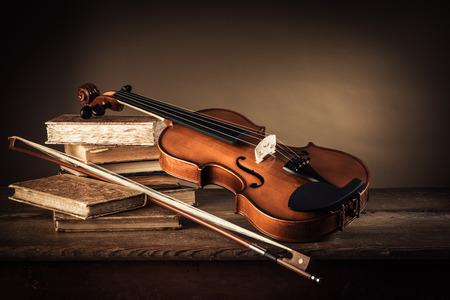 バイオリン、弓、素朴な木製のテーブル、芸術および音楽のコンセプト上の古い本