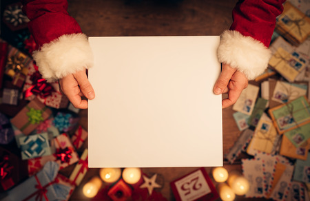 hand card: Santa Claus holding a blank sign, hands close up, top view, desktop with Christmas gifts and letters on background Stock Photo