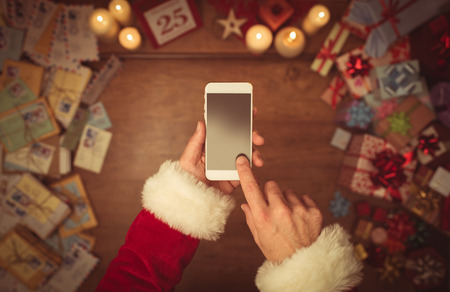 text: Santa Claus using a touch screen smart phone, hands close up, top view, desktop with gifts and Christmas letters on background