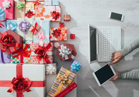 laptop computer: Man sitting at desk using a tablet and plenty of colorful gifts, celebrations and Christmas concept