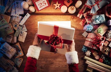 wow: Santa Claus la apertura de una caja de regalo de Navidad brillante magia, regalos y cartas de todo, vistas las manos arriba Foto de archivo