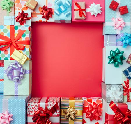 cajas navidad: Cajas de regalo de colores que enmarcan un espacio de la copia en blanco rojo en un escritorio, vista desde arriba, Navidad y celebraciones concepto Foto de archivo