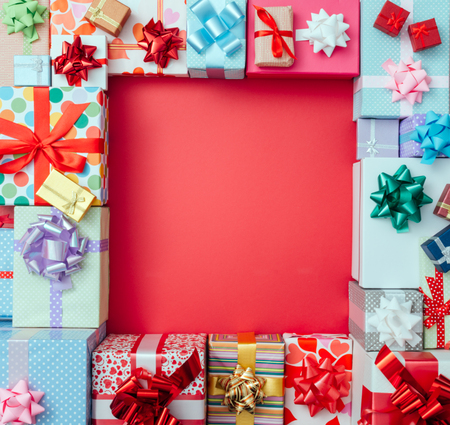 Colorful gift boxes framing a red blank copy space on a desktop, top view, Christmas and celebrations concept
