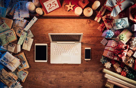 Christmas desktop with laptop, tablet and smart phone surrounded by gift boxes and letters, top view