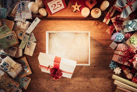 Apra il contenitore vuoto regalo di Natale su un tavolo di legno, circondato da lettere e regali, vista dall'alto