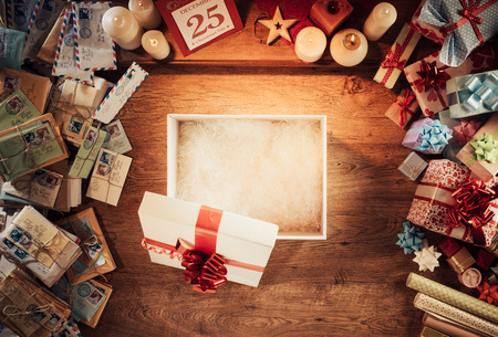 Open empty Christmas gift box on a wooden desktop surrounded by letters and presents, top view