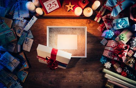 Open gift box met een lege witte kaart in, cadeaus en brieven van Kerstmis rond, desktop bovenaanzicht