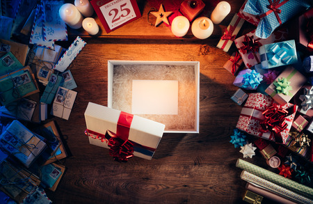 december: Open gift box with a blank white card inside, presents and Christmas letters all around, desktop top view Stock Photo