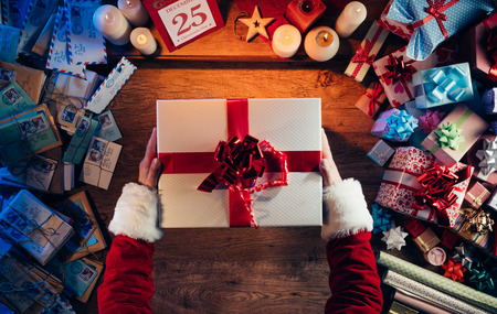 presents: Santa Claus holding a beautiful Christmas gift box, letters and presents all around, hands top view