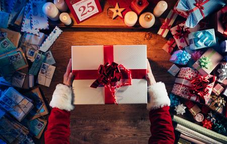 calendario diciembre: Santa Claus la celebración de una hermosa caja de regalo de Navidad, letras y presenta a su alrededor, con las manos vista superior