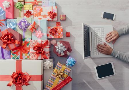 El hombre sentado en el escritorio utilizando un ordenador portátil con un montón de regalos coloridos, celebraciones y el concepto de Navidad