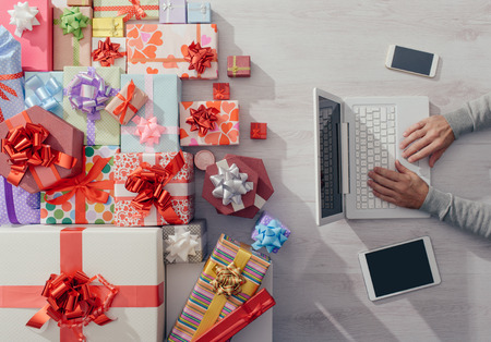 Man sitting at desk using a laptop with plenty of colorful gifts, celebrations and Christmas concept