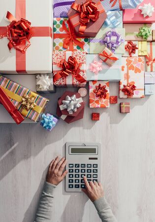 gift spending: Man calculating costs with a calculator and lots of colorful gift boxes, expensive Christmas concept Stock Photo