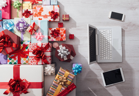christmas gifts: Laptop, tablet and smart phone on a desk with plenty of colorful gifts, celebrations and Christmas concept, top view Stock Photo