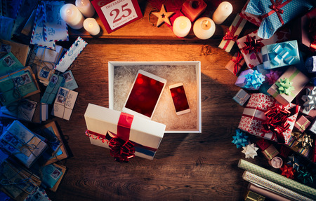 Open Christmas gift box with a tablet and a smart phone inside, presents and letters all around, top view Stockfoto