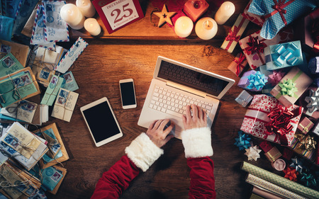Hi-tech Santa Claus working at his desk and typing on a laptop surrounded by gift boxes and Christmas letters, hands top view