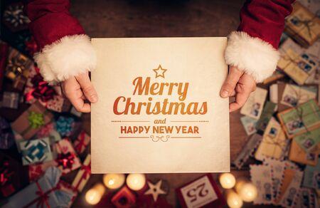 cajas navide�as: Santa Claus sosteniendo un papel viejo con mensaje de Feliz Navidad y Feliz A�o Nuevo Foto de archivo